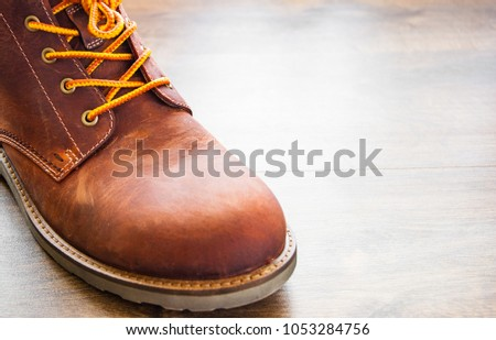brown leather boots shoes on the brown wooden table background.with copy space. #1053284756