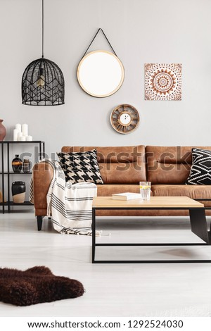 Brown leather couch with blanket and patterned cushions in real photo of bright living room interior with coffee table with lemon water and book and mirror, clock and poster on the wall #1292524030