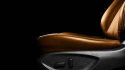 Brown leather interior of the luxury modern car. Perforated orange leather comfortable seats with stitching. Modern car interior details. Car detailing. Car inside