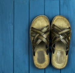 brown leather men's sandals on a wooden blue background