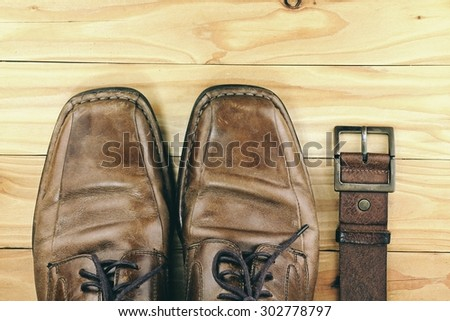 Brown leather men\'s shoes and belt on a wooden board. Men fashion. Men accessories. HDR.