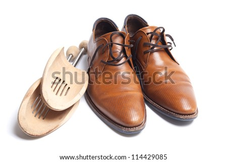 Brown leather mens shoes with wooden shoe stretchers on the side