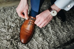 Brown leather shoe lacing. Businessman in white shirt and suit trousers. Groom getting ready for the wedding. Wearing clothes background. Dressing up male fashion.