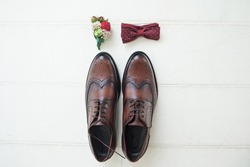 Brown leather shoes of the groom next to the boutonniere and the butterfly on a light background. Fees of the bridegroom for the wedding. Wedding concert. Wedding accessories for the groom.