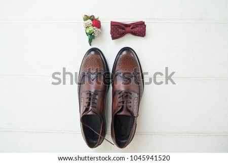 Brown leather shoes of the groom next to the boutonniere and the butterfly on a light background. Fees of the bridegroom for the wedding. Wedding concert. Wedding accessories for the groom. ストックフォト ©