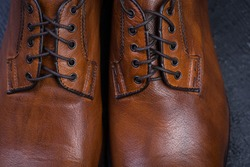 Brown leather shoes on a black wooden floor