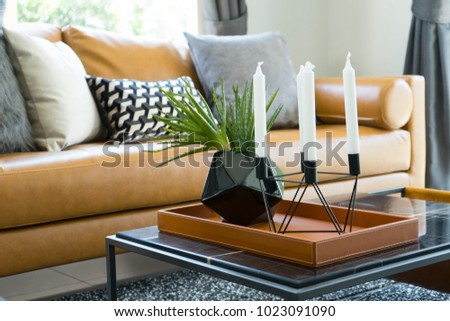 Brown leather sofa near a coffee table with black vase and modern candle holder.