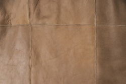 Brown leather surface stitched with threads. Natural material sample. Textured colorful background. Free space for advert.