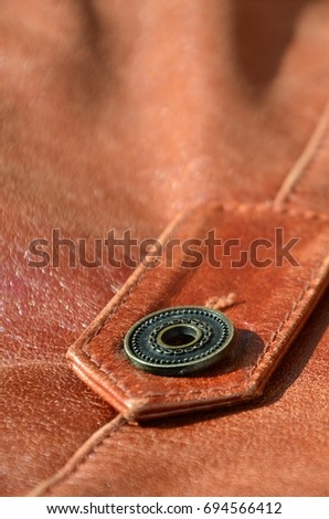 Brown leather texture. Useful as background for any design work. Macro photo of a button on outer clothing made of genuine leather #694566412