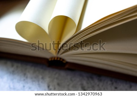 Brown leather vintage notebook blank pages open with pages wrapped in a heart shape form on bright white and gray concrete color texture table top with copy space. Education and studying concept. #1342970963