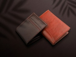 brown leather wallet on black background. view from above. studio shot. copy space for design. investment and savings concept.mockup realistic