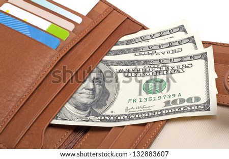 Brown leather wallet with credit cards and dollars isolated on white background