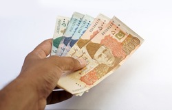 Brown man holding multiple pakistani currency notes on white background