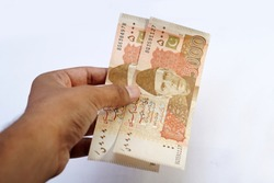 Brown man holding 5000 rupees pakistani currency note in hand