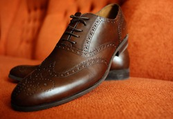 Brown man's shoes brogues on an orange background