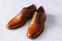 Brown men's leather shoes with black laces. White background. Wedding fashion.