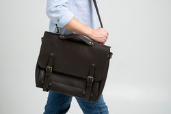 Brown men's shoulder leather bag for a documents and laptop on the shoulders of a man in a blue shirt and jeans with a white background. Satchel, mens leather handmade briefcase.