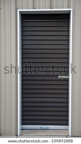 Brown metal door with padlock, of an outdoor storage unit