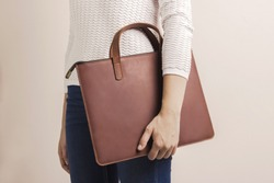 Brown modern unisex leather bag for laptop. Person holding case. Minimalist inclusion clothing concept