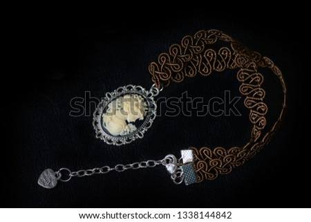 Brown necklace with girl cameo on a dark background close up #1338144842