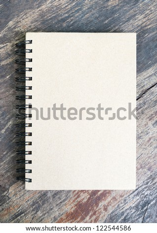 brown note book on grunge wood