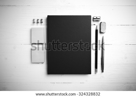 brown notebook with office supplies on white table view from above black and white style