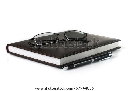 brown notebook with pen and glasses isolated on white