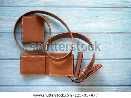 Brown nubuck leather with wallets and belt accessory set for men isolated on blue wooden background. Top view.