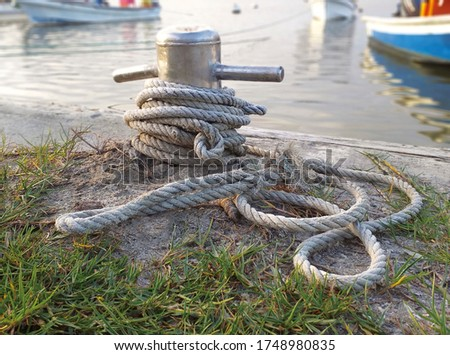 Brown old anchor rope wrapped around dock pier post. Anchor rope in the port, ship mooring tool. Close-up of textile rope on a pier. bollard in seaport. Grunge industrial rope.
