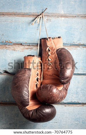 Brown old boxing gloves with a lace over old blue wall with peeling paint - stock photo