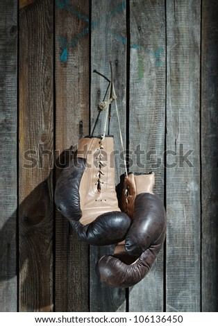Brown old boxing gloves with a lace over old wooden wall
