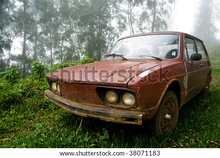 Brown old car abandoned in rural landscape with mist.