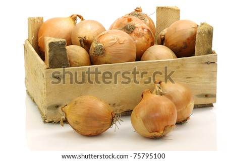 brown onions in a wooden crate on a white background