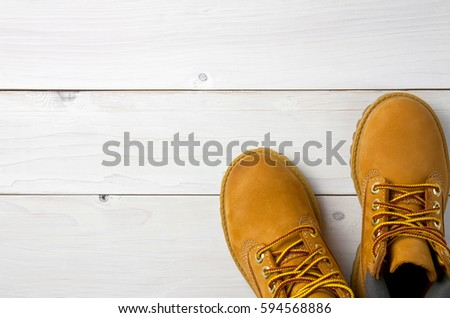 brown or yellow boots shoes for foot and adventure travel place on vintage white floor or table with copy space #594568886