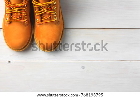 brown or yellow boots shoes for foot and adventure travel place on vintage white floor or table with copy space #768193795