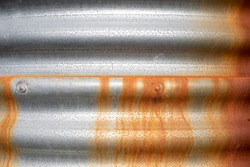 Brown/orange rust running down a silver/grey corrugated iron water tank in Victoria, Australia
