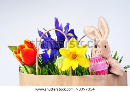 Brown package with flowers, eggs and a plush rabbit on a white background