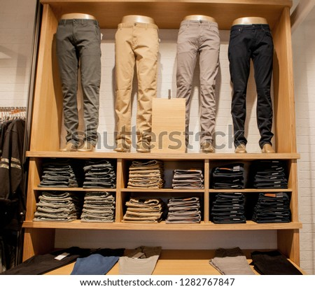 Brown pants on the store shelf. Brown pants collection pants stacked. #1282767847