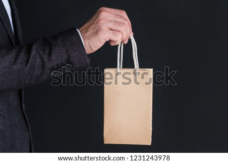 brown paper bag in man hand. shopping and consumerism concept.