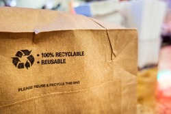 Brown paper bag that is 100% recyclable and reusable on a counter. A printed plea for user to recycle and reuse this bag as a form of packaging.