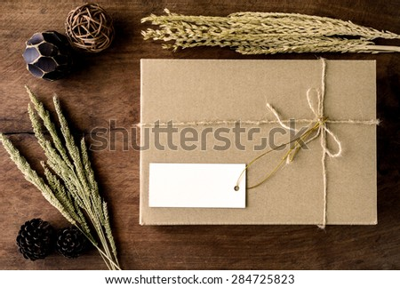 Brown paper box on old wood background with dried flower, Vintage tone