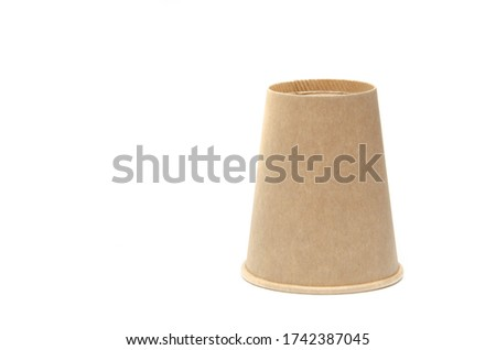 Brown paper cup for coffee, tea, a drink from environmental materials on a white background. One glass upside down on the right, bottom looking up