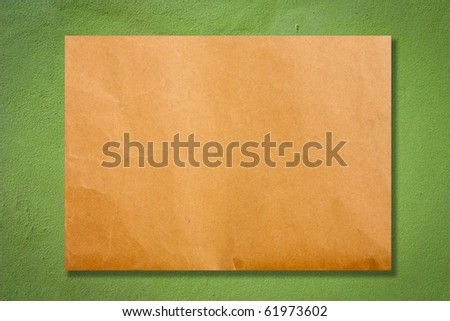 Brown paper on green cement wall
