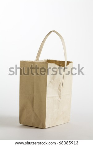 Brown paper shopping bag with handle isolated on a white background.
