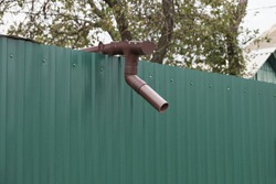 brown plastic gutter pipe on green metal fence wall outside