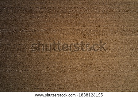 Brown plowed field. Brown background on the field aerial view. Earth top view. Сток-фото ©