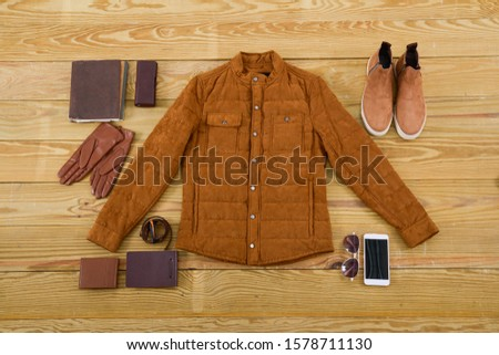 Brown purse, brown shoes,brown jacket,sunglasses, phone ,belt, gloves on a wooden board background