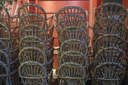 Brown rattan whicker chairs, cane-chairs stacked upon tables outdoor.