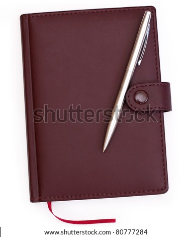 brown red leather notebook with pen