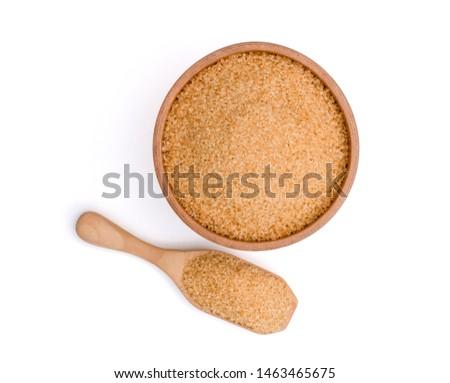 Brown refined granulated cane  sugar in wooden bowl and scoop isolated on white background with clipping path. Unhealthy food concept. Overhead view. Flat lay.